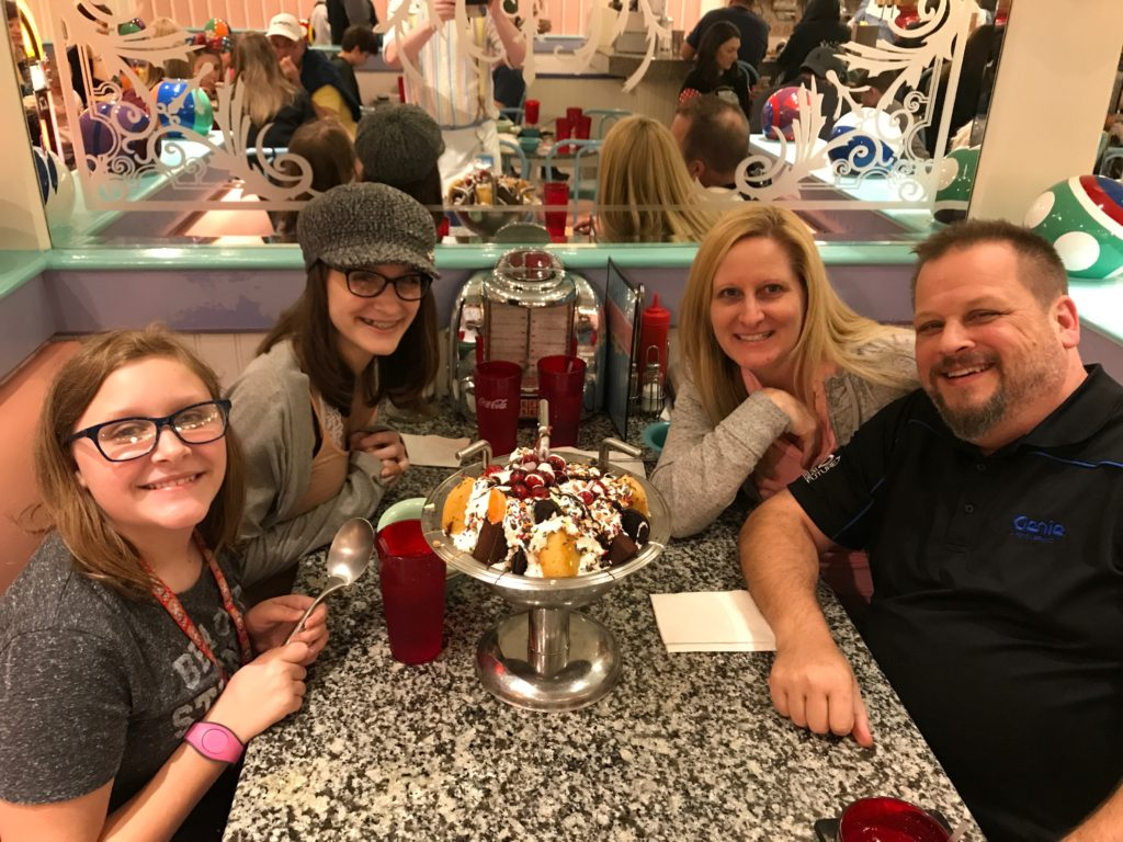 Parents with teen girls sitting at table with kitchen sink sundae at Disney's Beaches & Cream for a magical disney birthday