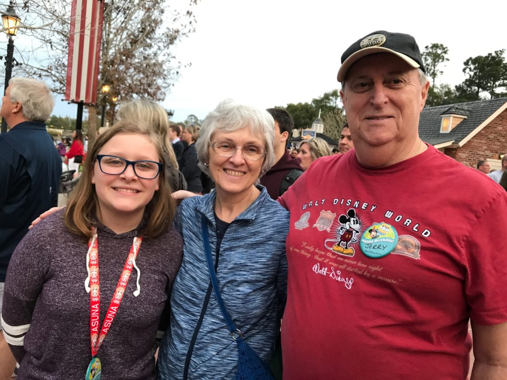 Teen girls standing with her grandparents and having a magical birthday at Disney