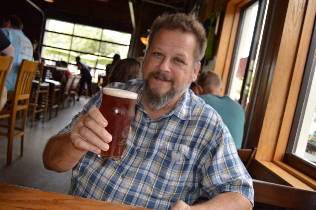Holding pint glass of beer at Sanford Brewing