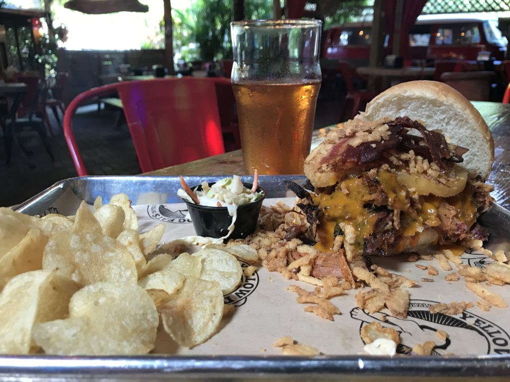Mr Smokey sandwich at Yellow Dog Eats with beer glass, and chips