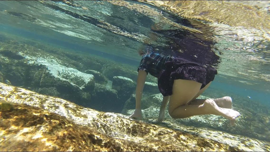 underwater view of  snorkeling girl kneeling on rocks overlooking deep spring