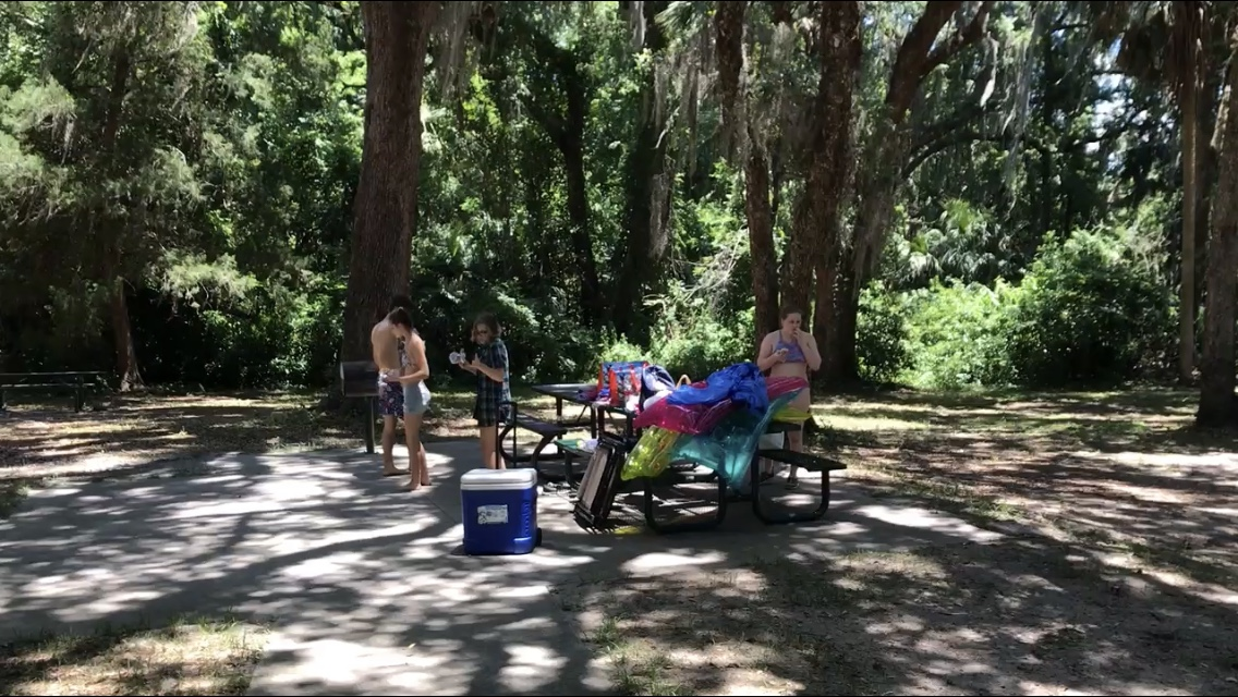 kids standing at picnic tables in shade