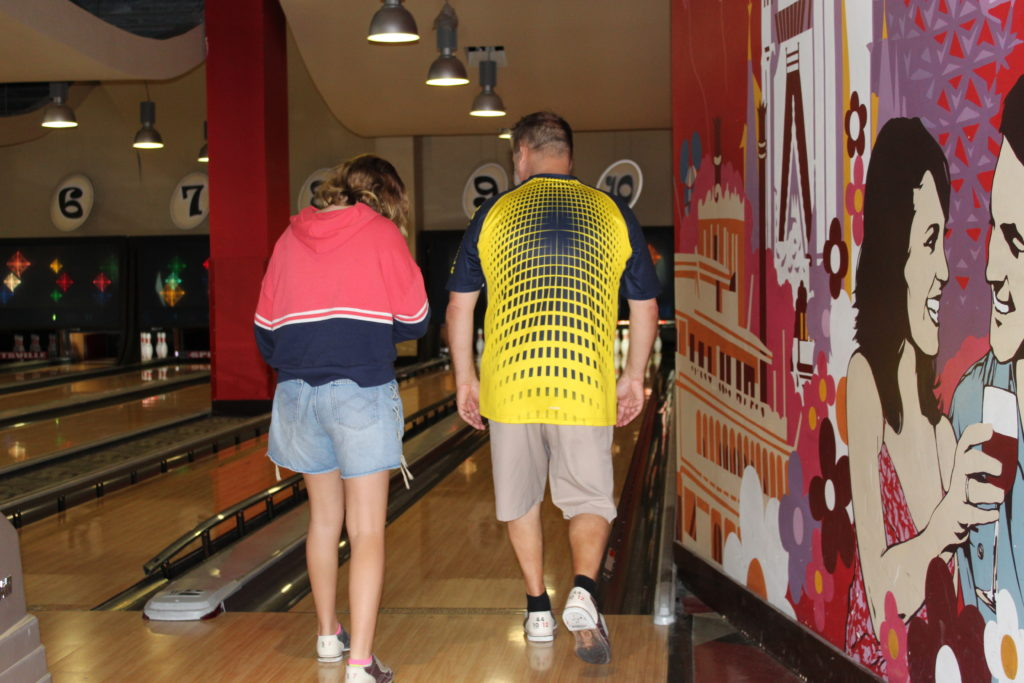 dad showing daughter how to bowl and make lasting memories at Splitsville