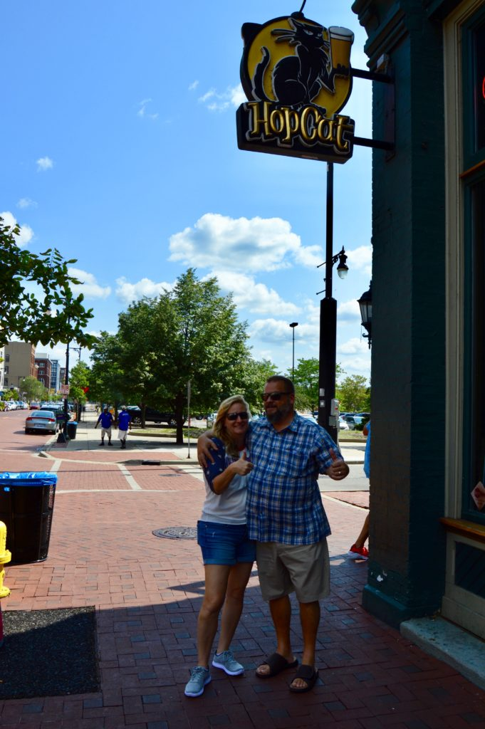 Man & woman standing under HopCat sign in Beer City, USA