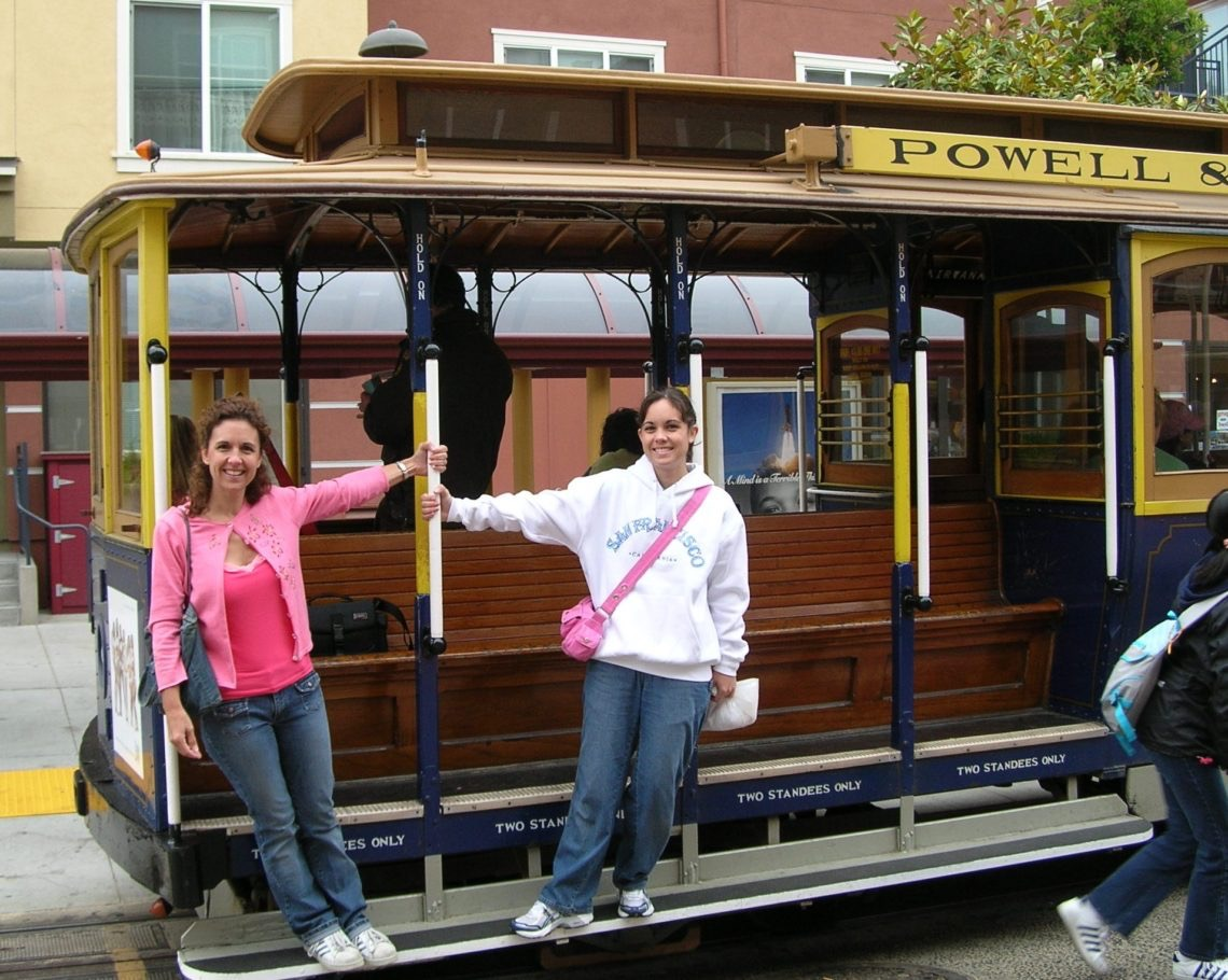 Two ladies holding onto the rails of a trolley