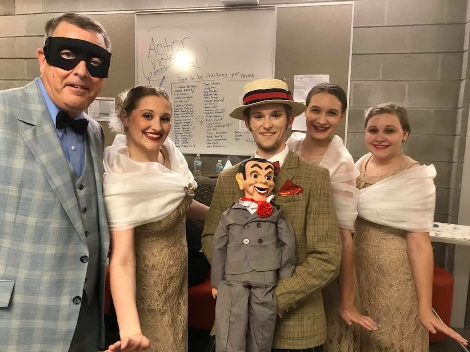 Man with eye mask in suit, man with ventriloquist doll, and three young ladies in lacey dresses.