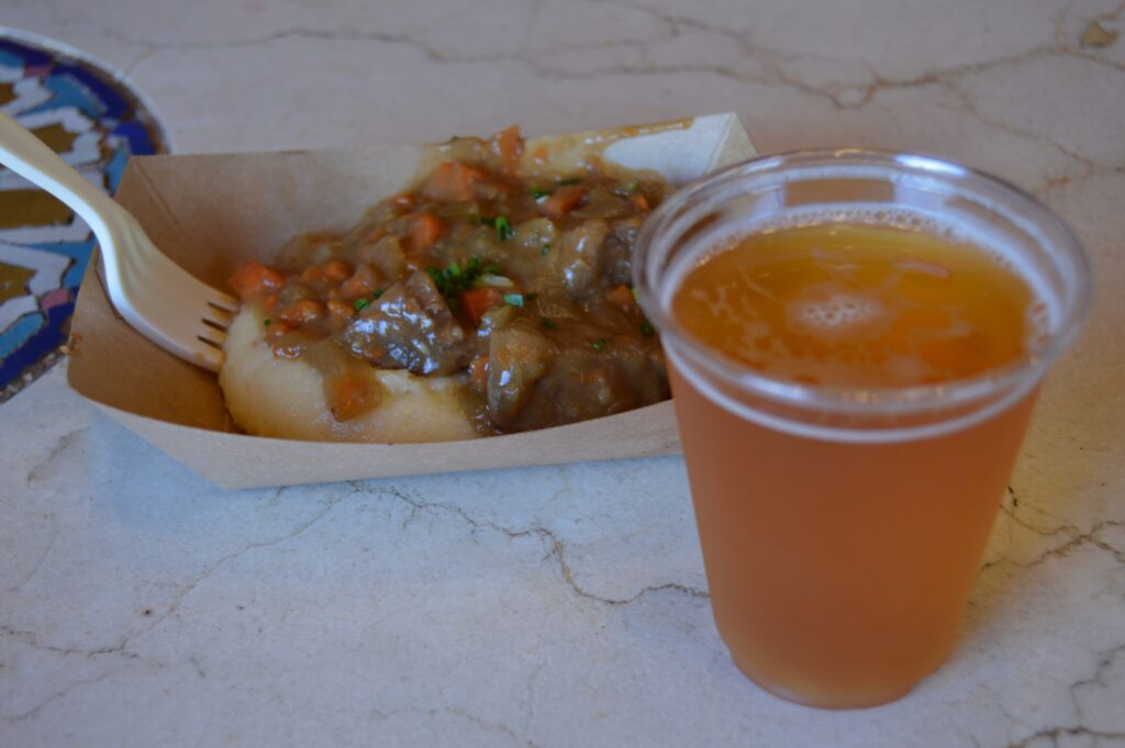 stew over mashed potatoes with a glass of beer