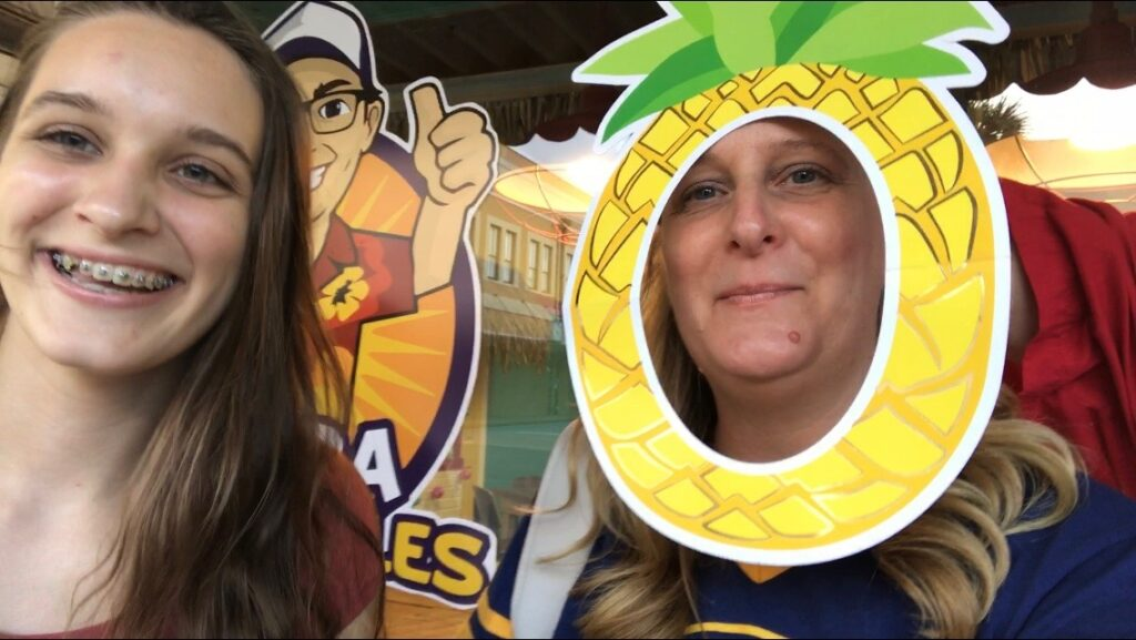 Mom and daughter with photo booth pineapple frame.