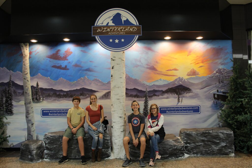 Teens sitting for photo outside of Winterland Adventures