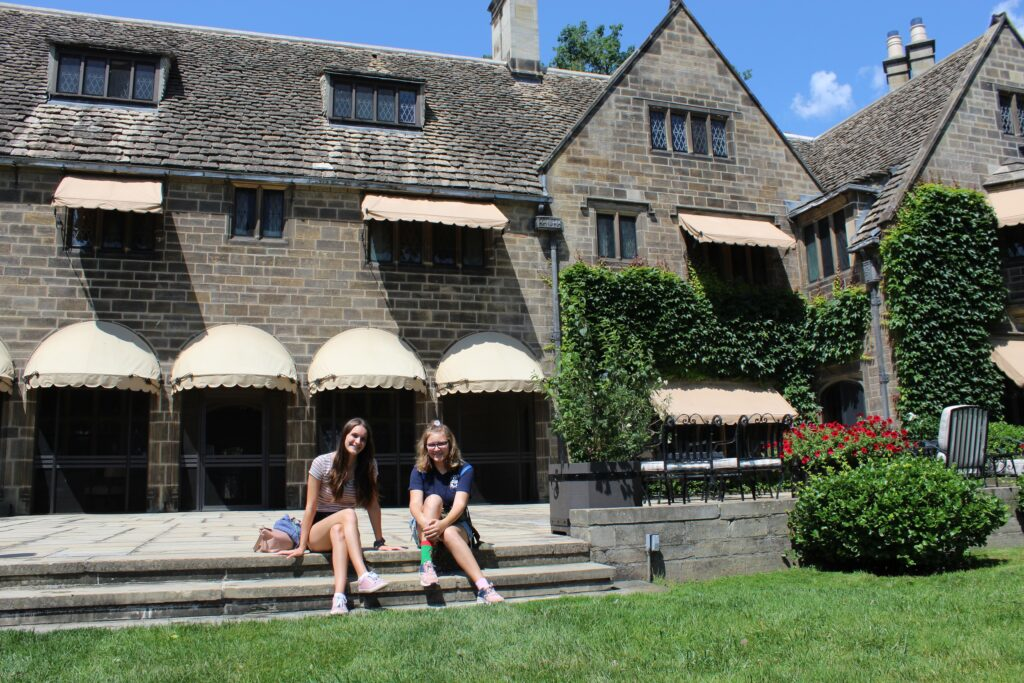 Teens sitting on porch steps outside back of Ford House, home of Edsel Ford