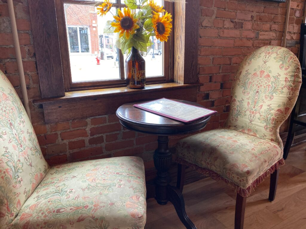 Antique table and chairs with brick wall behind