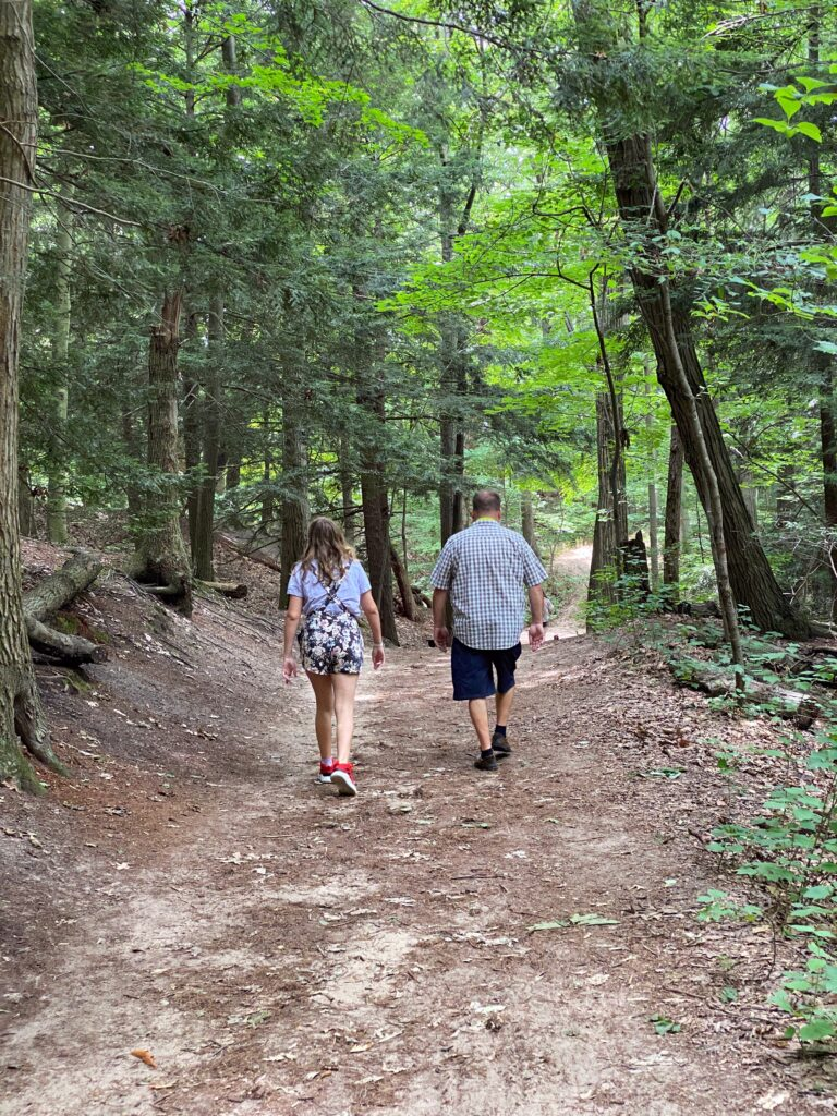 mand and daughter walking trail in Saugatuck Dunes State Park